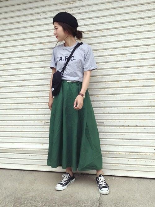 ロゴTシャツにグリーンギャザースカートを履いた女性