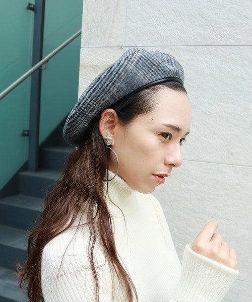 白ニットにベレー帽をかぶった女性