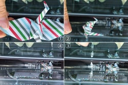 ガラス張りの空間から折り鶴を落とすとどんどん下から積み重なっていくコンセプト(C)モデルプレス