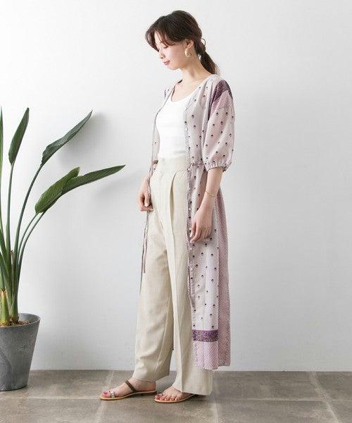 白のタンクトップにベージュのパンツを合わせて、エスニック柄の前ボタンワンピースを羽織った女性