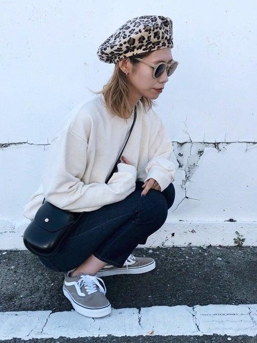 白のスウェットにデニムを合わせて、レオパード柄のベレー帽をかぶった女性