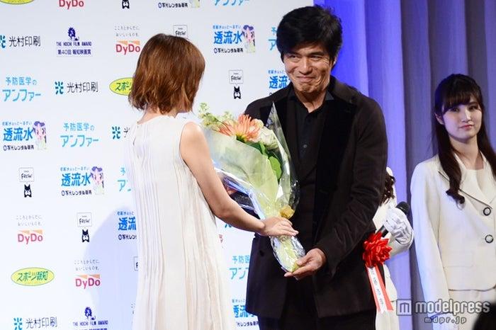 佐藤浩市(右)に花束を贈呈する本田翼(左)