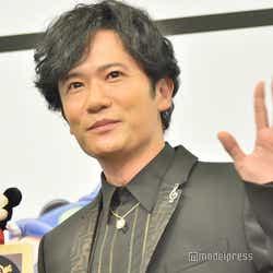 ポスターの上のミッキーが落ちないように一生懸命支えながらも笑顔を浮かべる稲垣吾郎(C)モデルプレス