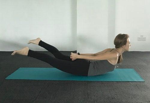 体の後ろで両手を握り、さらに肩甲骨を中央に寄せて胸を高く引き上げます。