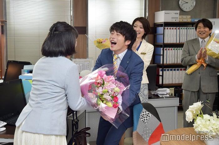 まいまい(伊藤修子)の笑い方を真似しながら近づき、花束を手渡す田中圭。(C)モデルプレス