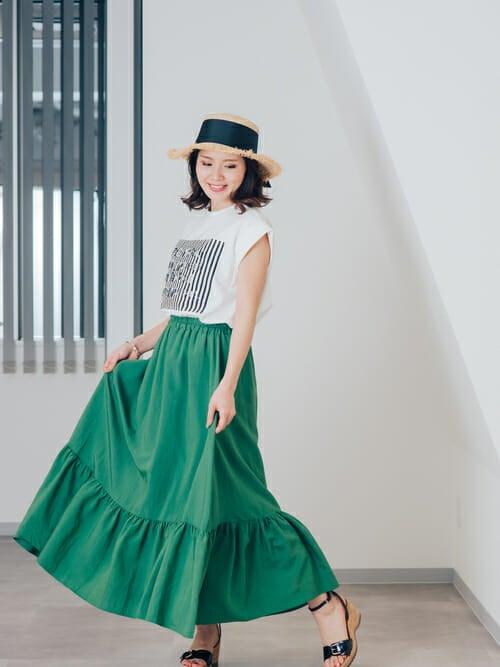 白のロゴTにグリーンのペプラムスカートを履いた女性