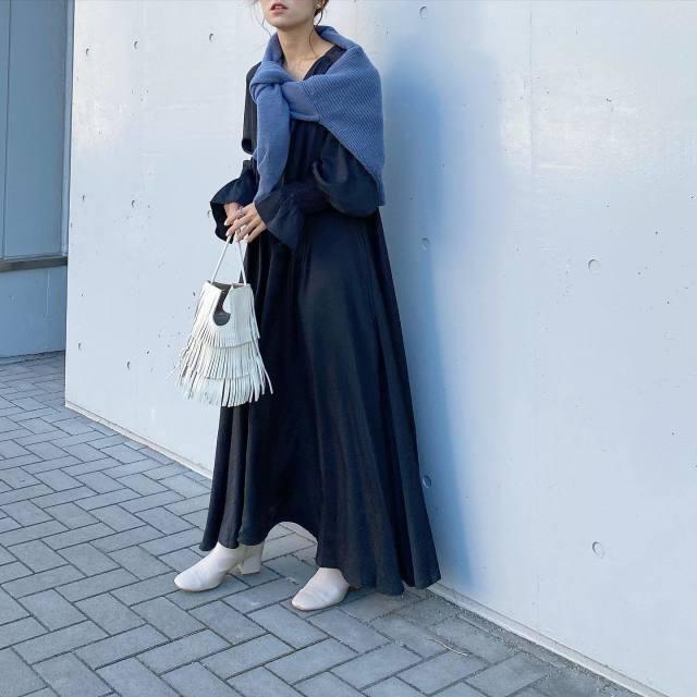 黒のワンピースにブルーのカーディガンを羽織り、白のスクエアブーツとフリンジハンドバッグをコーディネート