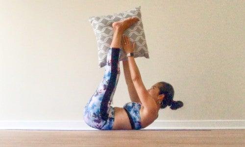 息を吐きながら両手両足を同時に持ち上げて、クッションもしくは枕を両足に渡すようにします。