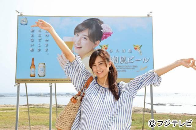「みさき潮風ビール」の看板前で笑顔でポーズする山本美月/月9ドラマ「SUMMER NUDE」より