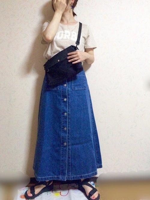 ベージュのロゴTにデニムボタンスカートを履いた女性