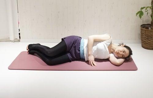 横向きに寝て、背骨を伸ばすようなポーズをとります