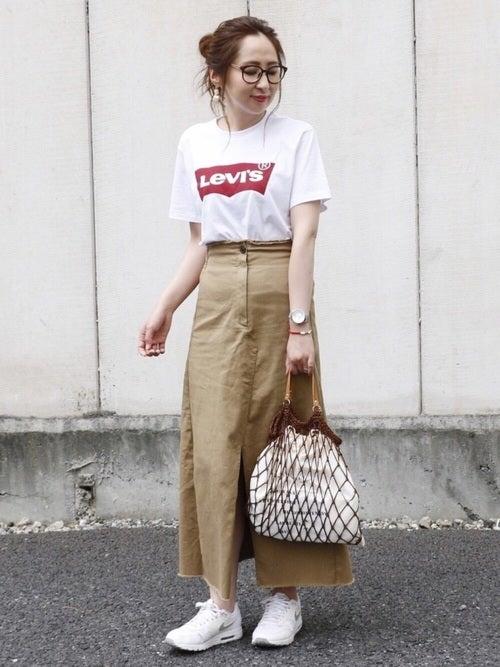 ロゴTシャツにチノスカートを履いた女性