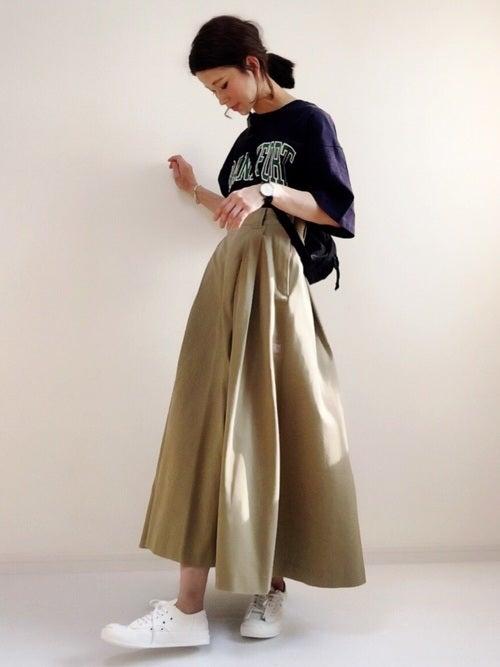 ネイビーのロゴTにベージュのチノスカートを履いた女性