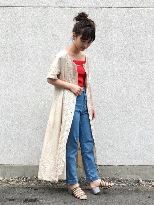 赤のキャミソールにデニムを合わせて、白の刺繍入り前ボタンワンピースを羽織った女性