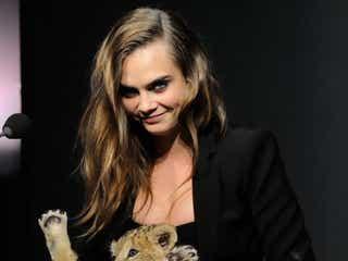 カーラ・デルヴィーニュ、ライオンの赤ちゃんを抱いて不敵な笑み
