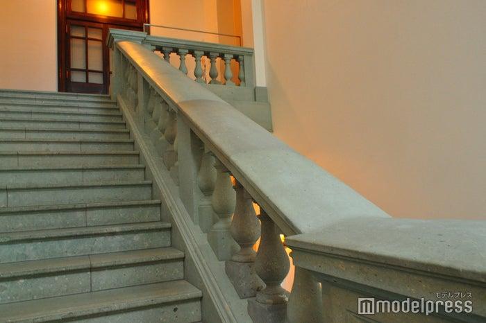 階段の手すりや欄干の一部分だけ色が違うのは旧三菱一号館の保存部材を使用しているから/明治期の石材は伊豆の青石、2000年代の復元時には中国の五雲石が使われた(C)モデルプレス