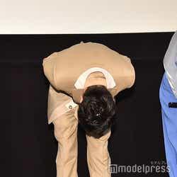 バミリに頭が届きそうなくらいまで深くお辞儀をする田中圭(C)モデルプレス