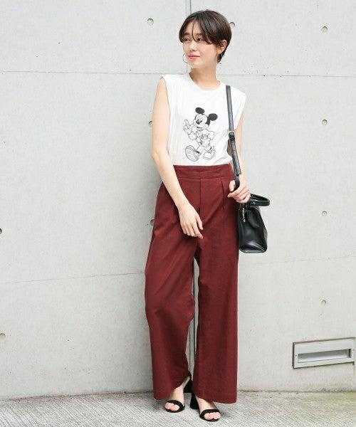 ミッキーノースリにブラウンパンツを履いた女性