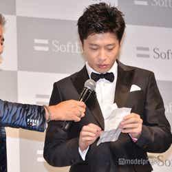 半信半疑で紙を広げる田中圭(C)モデルプレス