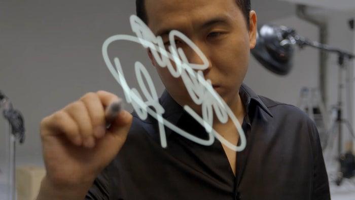 サインをする斎藤さん(提供画像)