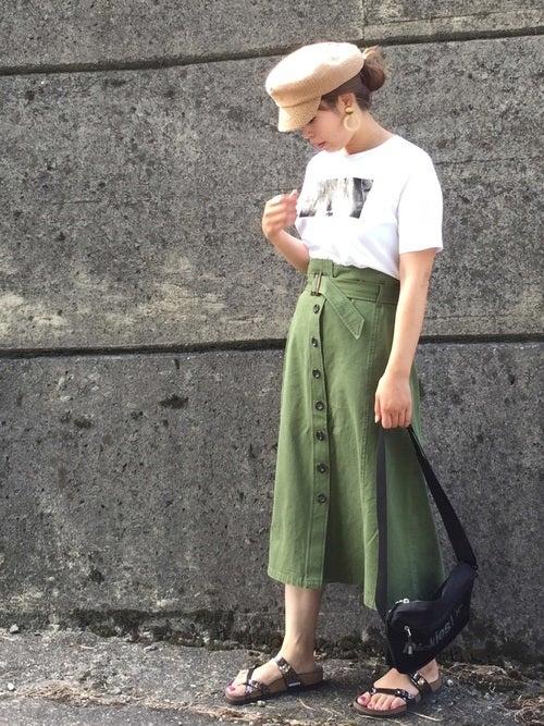 白のプリントTシャツにカーキのボタンスカートを履いた女性