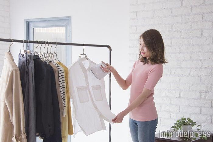 ハンガーにかけたまま衣類にアイロン面を直接当て、ゆっくりと滑らせていく(C)モデルプレス
