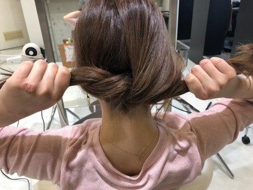 分けた髪を紐をしばるように結びます。