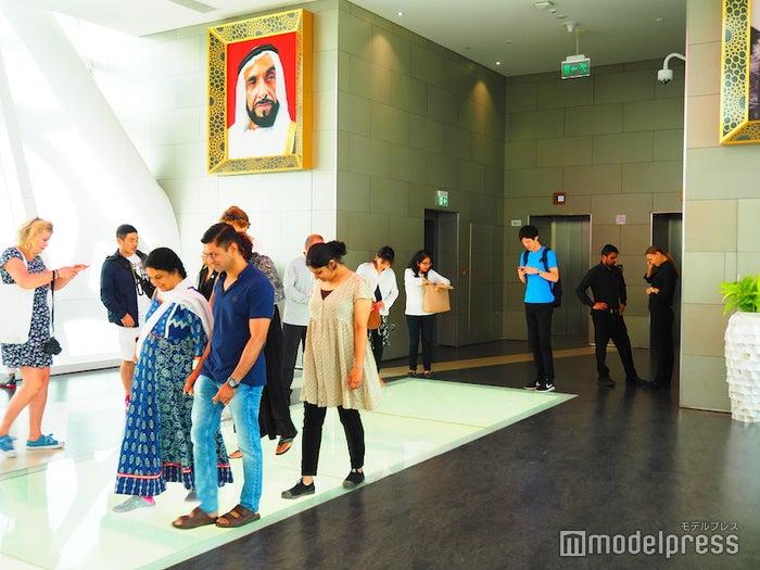 ガラス張りの床を覗きながら歩く観光客たち(C)モデルプレス