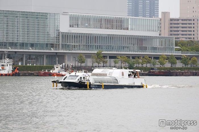 信濃川の河口から船に乗って登場(C)AKS