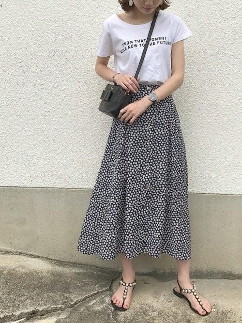 ロゴTシャツに柄スカートを履いた女性