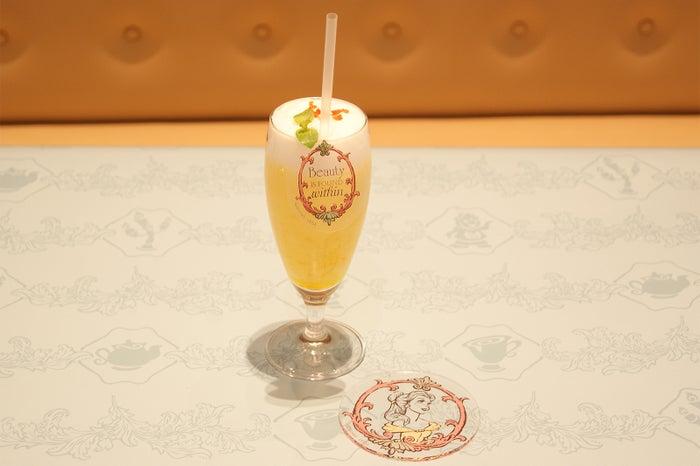 <ベル>マンゴースムージー890円/コースター付き1,590円(C)Disney