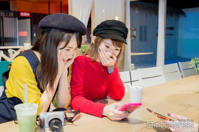 撮影してもらった写真を見て思わず笑ってしまう菊田さん(C)モデルプレス