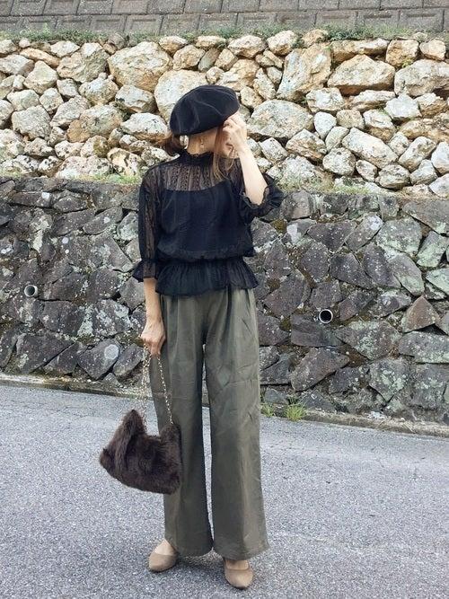 黒のレースブラウスにカーキのワイドパンツを合わせて、コーデュロイの黒のベレー帽をかぶった女性