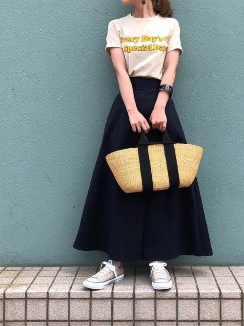 ベージュのロゴTにネイビーのチノフレアスカートを履いた女性