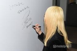 サインをするローランド(ROLAND)/(C)モデルプレス