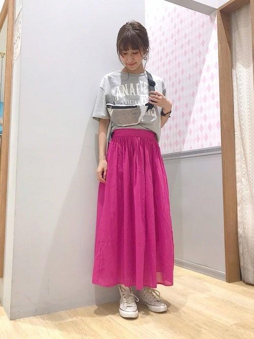 グレーのロゴTにピンクのギャザースカートを履いた女性