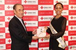 募金を寄付する様子/(左から)大塚義治氏、宮本エリアナさん