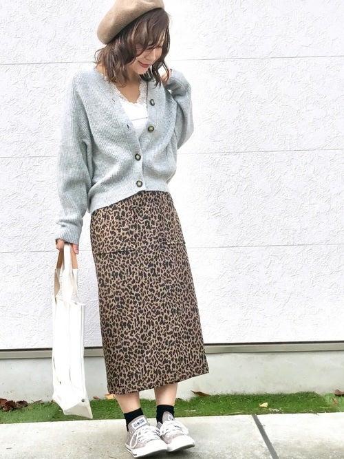 白のタンクトップにグレーのニットカーデを羽織ってレオパード柄のスカートを履き、ベージュのベレー帽をかぶった女性