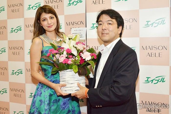 花束を受け取るマギー(左)/「MAISON ABLE」ブース
