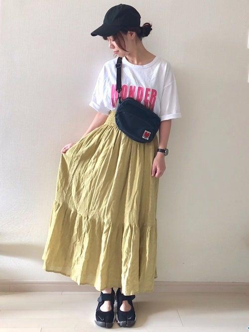 白のロゴTに黄色のマキシスカートを履いた女性