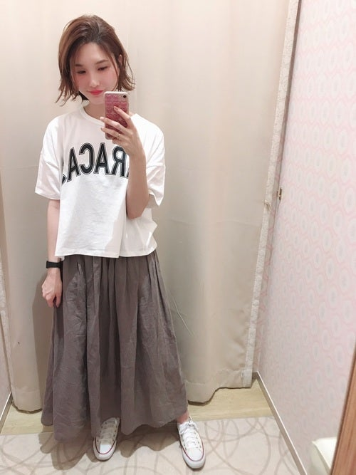白のロゴTにベージュのギャザースカートを履いた女性