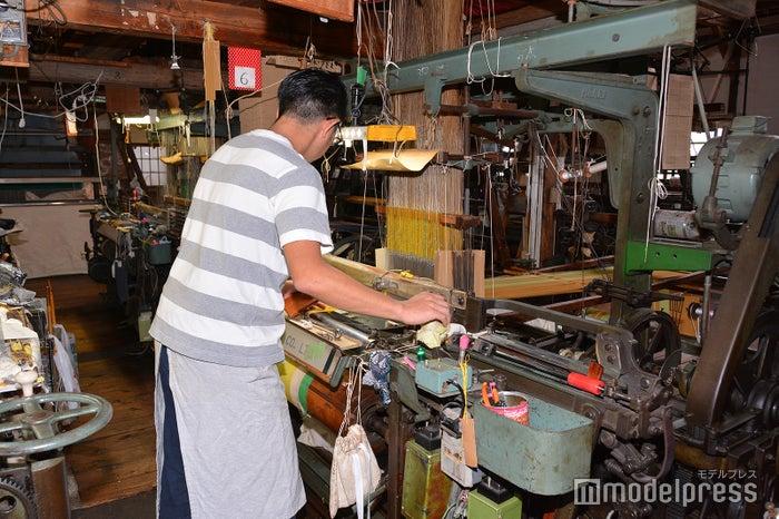 旧式のジャカード式シャトル織機でひとつひとつ手間暇かけて織られる(C)モデルプレス