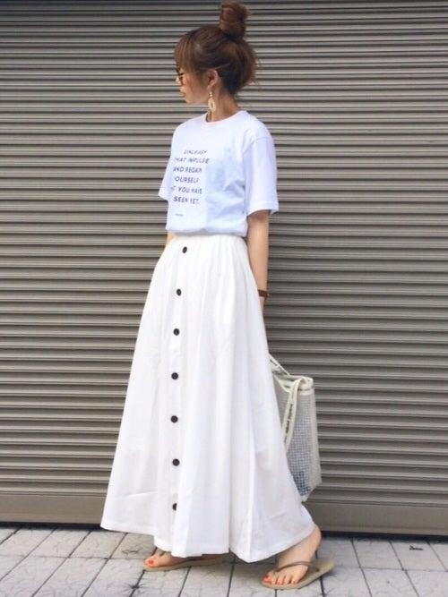 白のロゴTに白のボタンスカートを履いた女性