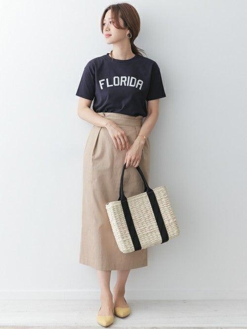 ロゴTシャツにチノタイトスカートを履いた女性