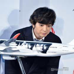 メンバーの顔が塗装された機体の模型を愛しそうに見つめる松本潤(C)モデルプレス