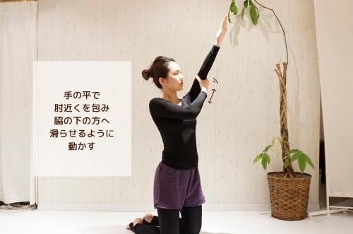 手の平で肘近くを包み脇の下の方へ滑らせるように動かす
