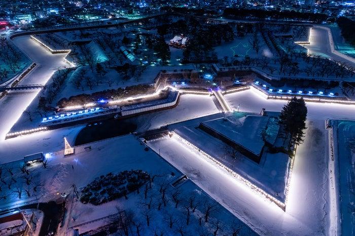 ライトアップされた積雪の五稜郭/photo by ぱくたそ