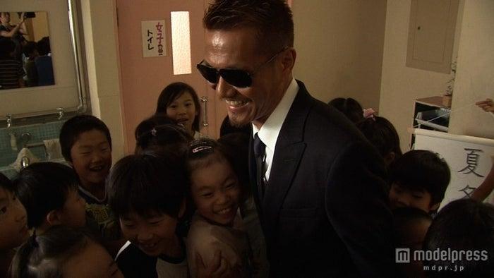 母校の小学校の式典を訪れた際、子どもたちから囲まれるATSUSHI(C)NHK