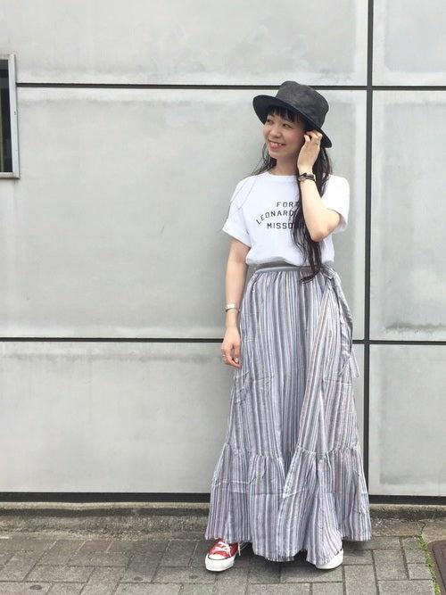 白のロゴTにストライプ模様のペプラムスカートを履いた女性