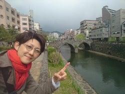 長崎の眼鏡橋の前で丸眼鏡をかけて(提供写真)